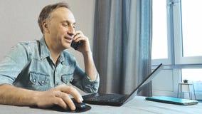 Um homem trabalha em casa em um portátil e na fala no telefone Vista da parte inferior vídeos de arquivo