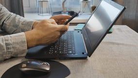 Um homem trabalha em casa em um portátil e na fala no telefone Vista da parte inferior video estoque