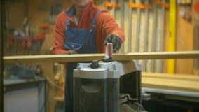 Um homem trabalha em uma oficina com uma máquina do woodworking filme