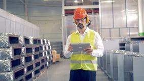 Um homem trabalha na facilidade industrial, verificando a informação em sua tabuleta video estoque
