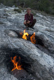 Um homem turco aquece sua mão ao lado das rochas flamejantes do peixe-rato situado perto de Cirali na costa mediterrânea de Turqu Fotos de Stock