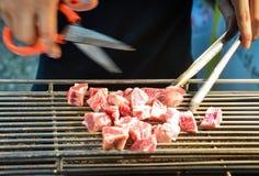 Um homem usa um corte das tesouras e fatia do cozimento na grelha de carne crua no fogão elétrico foto de stock royalty free