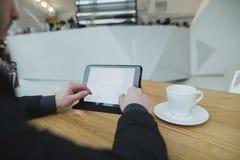 Um homem usa o Internet com uma tabuleta que senta-se em um café para uma xícara de café Fotografia de Stock