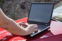 Um homem usa um portátil na capa de um carro foto de stock