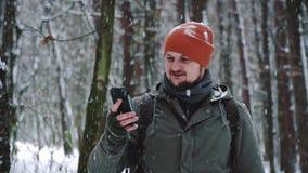 Um homem usa um telefone celular em redes sociais de uma floresta nevado, v?deos de observa??o, fazendo apostas, rindo e exultand vídeos de arquivo