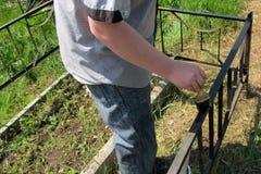 Um homem usa uma escova para pintar uma cerca do ferro com cor preta fotos de stock royalty free