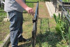 Um homem usa uma escova para pintar uma cerca do ferro com cor preta fotos de stock