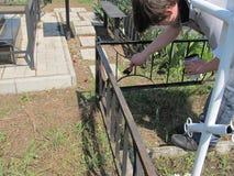 Um homem usa uma escova para pintar uma cerca do ferro com cor preta imagens de stock