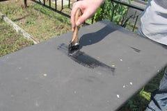 Um homem usa uma escova para pintar uma tabela do ferro com cor preta fotos de stock royalty free