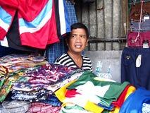 Um homem vende camisas coloridas sortidos e calças Fotografia de Stock