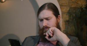 Um homem vermelho-farpado novo obtém más notícias em um smartphone filme