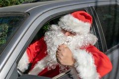 Um homem vestido como Santa Claus entrega presentes no carro Problemas do esforço e da estrada imagens de stock royalty free