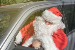 Um homem vestido como Santa Claus entrega presentes no carro Problemas do esforço e da estrada imagem de stock royalty free