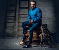 Um homem vestido no calças de brim, camisa azul e laço senta-se em um woode imagens de stock royalty free