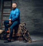 Um homem vestido no calças de brim, camisa azul e laço senta-se em um woode foto de stock royalty free