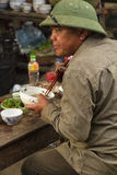 Um homem, vestindo um chapéu, toma seu café da manhã em Bac Ha Imagens de Stock Royalty Free