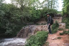 Um homem, um viajante em um casaco de cabedal e um chapéu de vaqueiro Grande cachoeira defluxo com água suja, uma viagem, um luga foto de stock