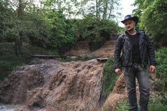 Um homem, um viajante em um casaco de cabedal e um chapéu de vaqueiro Grande cachoeira defluxo com água suja, uma viagem, um luga imagem de stock
