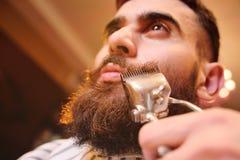 Um homem viril novo com uma barba no barbeiro Imagens de Stock