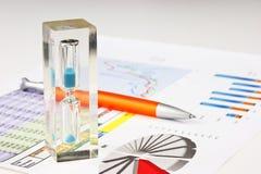 Um hourglass e um diagrama fotografia de stock