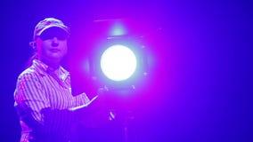 Um iluminador da jovem mulher dirige um feixe de luz de um projetor do perfil no sal vídeos de arquivo
