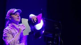 Um iluminador da jovem mulher dirige na cena o feixe de um projetor do perfil vídeos de arquivo