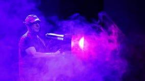 Um iluminador do homem dirige um feixe do projetor claro do perfil da cena no sal?o em um sopro de fumo filme