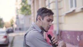 Um indivíduo alegre novo considerável está andando na cidade Braços de ondulação de corrida Escuta a m?sica em fones de ouvido Mo video estoque