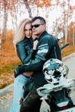 Um indivíduo atrativo e uma jovem mulher em um equipamento de couro preto com uma motocicleta foto de stock royalty free