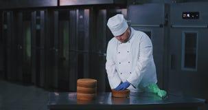Um indivíduo bonito ronco do padeiro com vestuário apropriado dos cozinheiros chefe corta o bolo na metade e nas verificações par vídeos de arquivo
