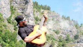 Um indivíduo com uma barba em uma camisa preta e em óculos de sol finge jogar uma guitarra acústica fumarento Vídeo engraçado est filme