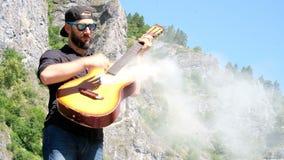 Um indivíduo com uma barba em uma camisa preta põe sobre óculos de sol e finge-os jogar uma guitarra acústica de que o fumo vem D vídeos de arquivo