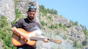 Um indivíduo com uma barba finge jogar uma guitarra acústica de que o fumo vem Vídeo estranho sobre um músico da rocha na naturez vídeos de arquivo