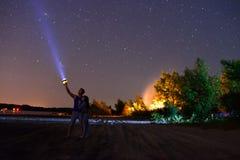 Um indivíduo com uma menina brilha uma lanterna elétrica no céu Fotografia de Stock