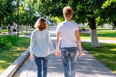 Um indivíduo com uma menina no verão no parque que guarda as mãos que anda no parque acampar O conceito do amor e da felicidade imagens de stock