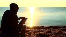 Um indivíduo com uma tabuleta que senta-se na praia do cascalho na frente do mar video estoque