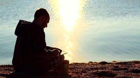 Um indivíduo com uma tabuleta que senta-se na praia do cascalho na frente do mar filme