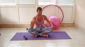 Um indivíduo considerável brincalhão em um t-shirt cor-de-rosa e em umas caneleiras azuis é contratado na aptidão que descreve um vídeos de arquivo