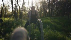 Um indivíduo considerável treina em um parque entre árvores finas Crossfit Balance as cordas Metragem extremamente próxima das co vídeos de arquivo