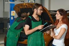 Um indivíduo do mecânico em um terno verde tenta reparar o motor do foto de stock royalty free