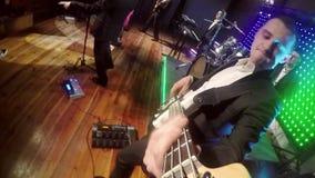 Um indivíduo dos jovens joga uma guitarra-baixo em uma cena iluminada colorida video estoque