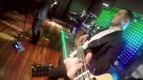 Um indivíduo dos jovens joga uma guitarra-baixo em uma cena iluminada colorida vídeos de arquivo