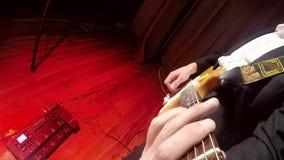 Um indivíduo dos jovens joga uma guitarra em uma cena iluminada colorida video estoque