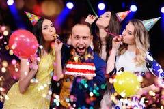 Um indivíduo e três meninas exultam e comemoram o partido no clube noturno Imagem de Stock
