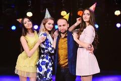 Um indivíduo e três meninas exultam e comemoram o partido no clube noturno Imagens de Stock