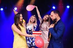 Um indivíduo e três meninas exultam e comemoram o partido no clube noturno Fotografia de Stock