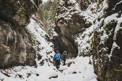 Um indivíduo e uma menina estão andando ao longo de um canyo coberto de neve da montanha foto de stock royalty free