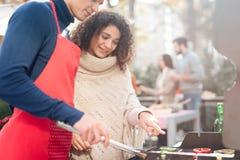 Um indivíduo e uma menina estão cozinhando o alimento do assado durante um piquenique com amigos imagem de stock royalty free