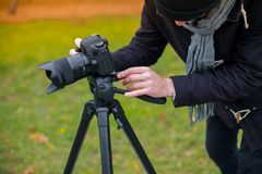 Um indivíduo em um parque ajusta-se - acima de uma câmera para fotografar algo fotografia de stock