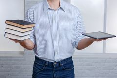 Um indivíduo em uma mão que guarda uma pilha de livros e de uma tabuleta imagem de stock